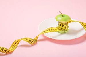 Apple core with measuring tape in place of the waist on a white plate on a pink background. Diet, weigh loss, starvation, fitness concept.